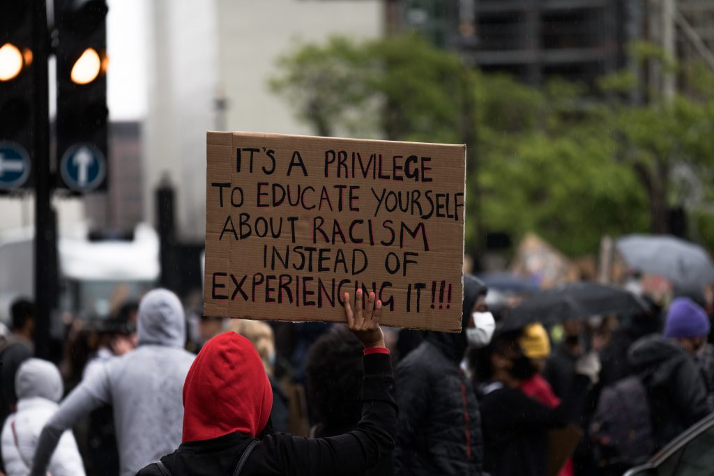 People holding an antiracist placard at a Black Lives Matter protest.
