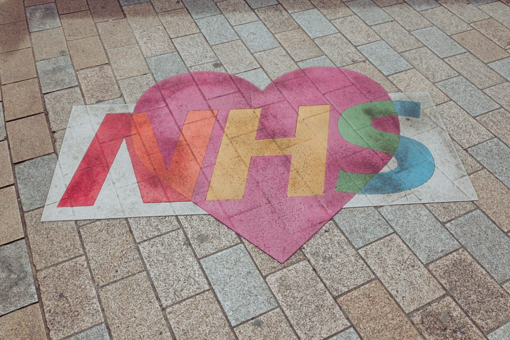 A colourful NHS logo over a pink heart, painted on the ground. Photo by Nicolas J Leclercq on Unsplash.